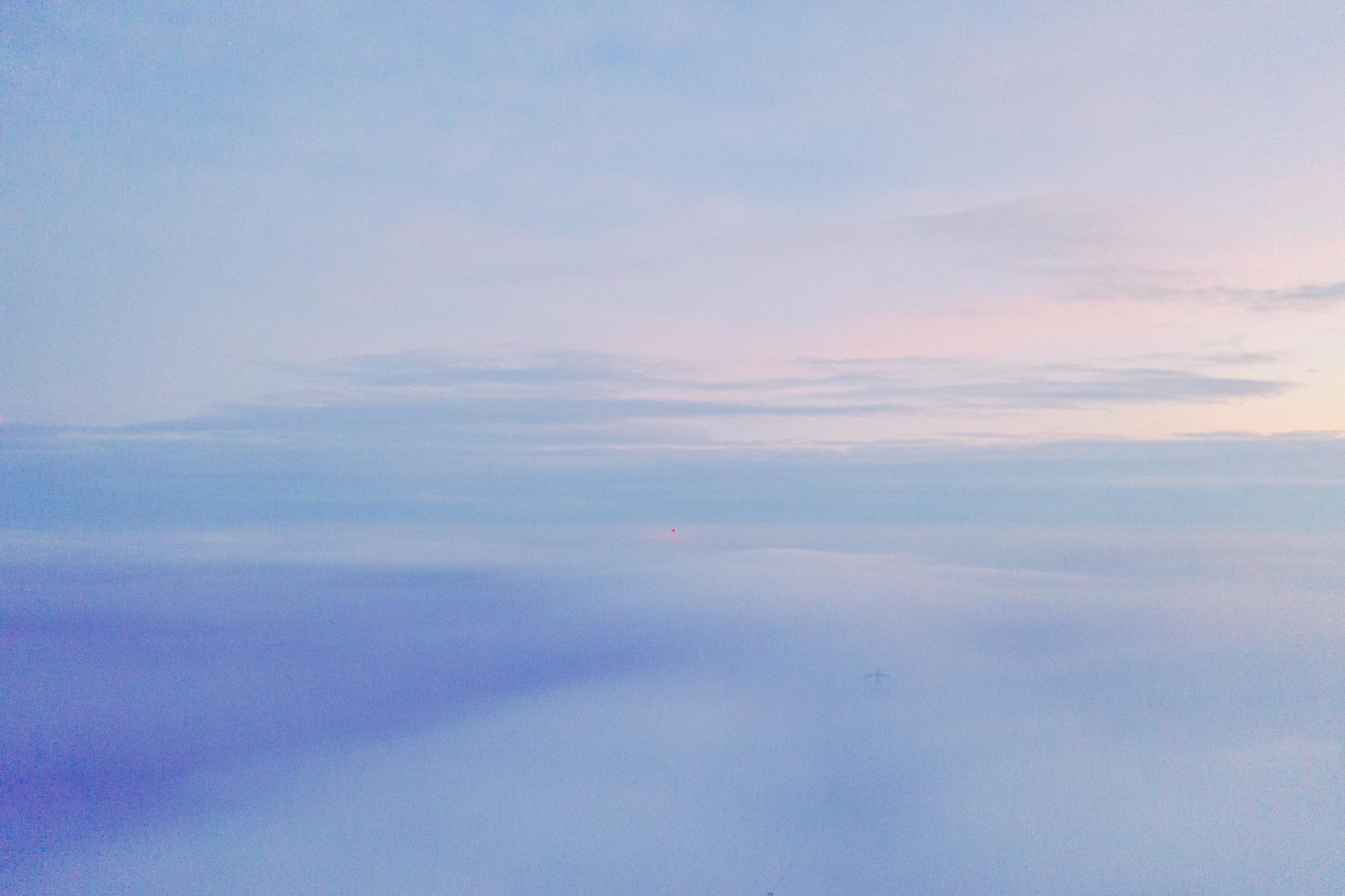 A red light in the background of a misty drone shot above the clouds