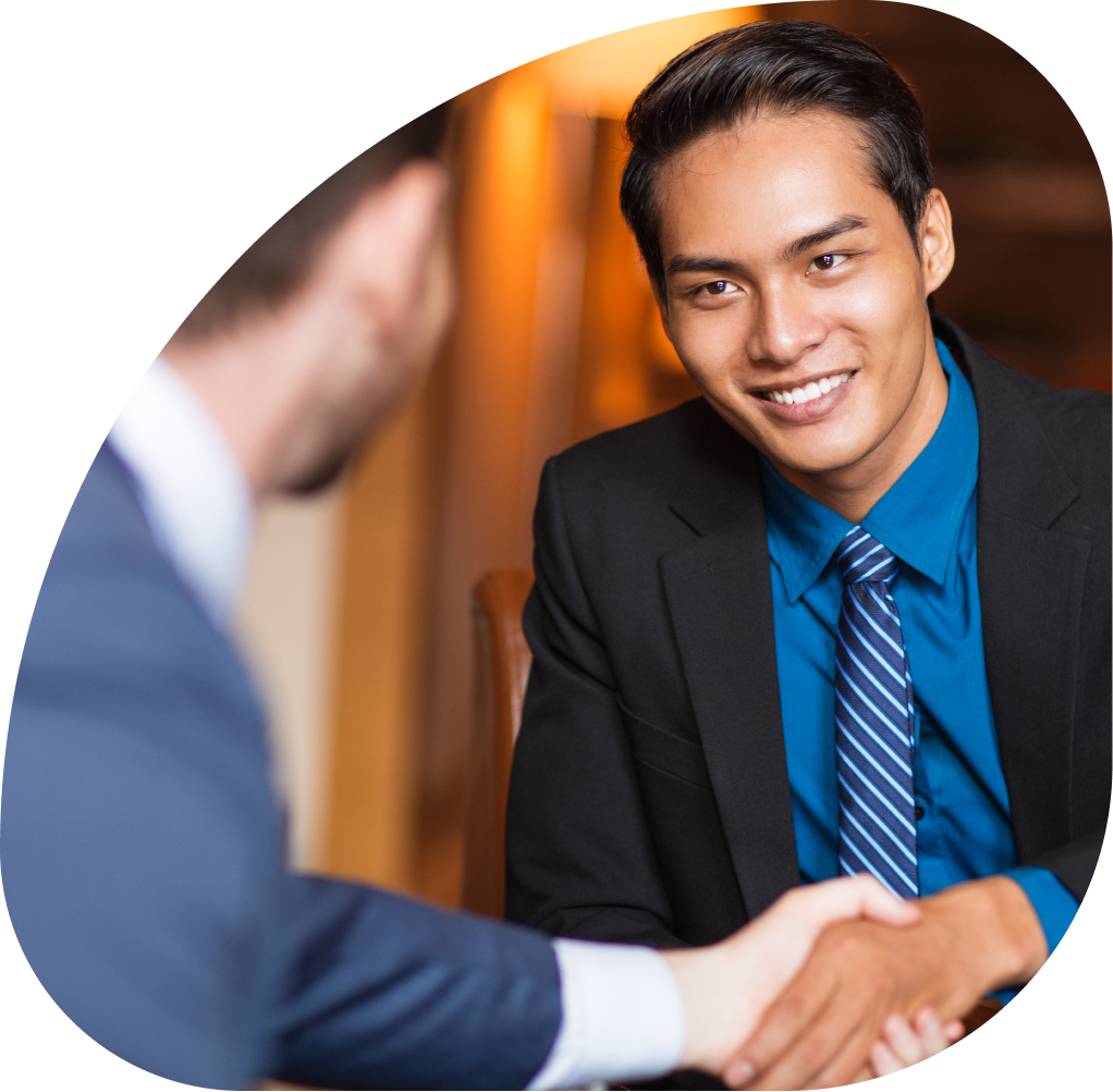 Two people shaking hands and one of them seem to be smiling.