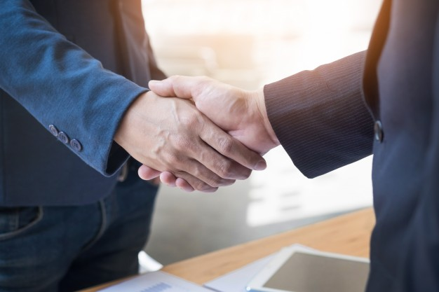 Two confident business man shaking hands during meeting office success dealing greeting partner
