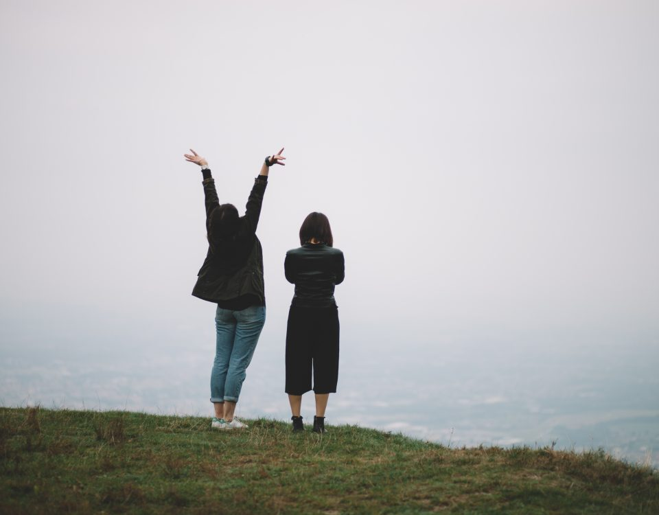 hiking vacation two women on a cliff edge looking out to see. one with folded arms and the other with arms in the air. dressed warmly in jeans and thick cardigans. grey sky, green grass foggy pale blue sea