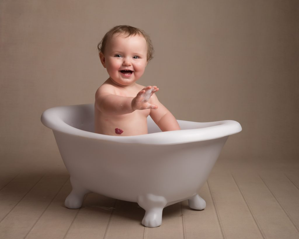 Alyssa sat in a mini free standing bath smiling at the camera holding out her hand with bubbles on the end