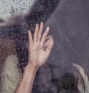 girl woman crying at a window with rain on it and hand on window