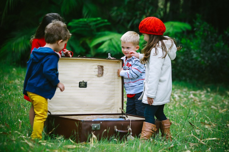 4 children gathered round and open old empty suitcase dressed in hats and coats in the middle of a green field