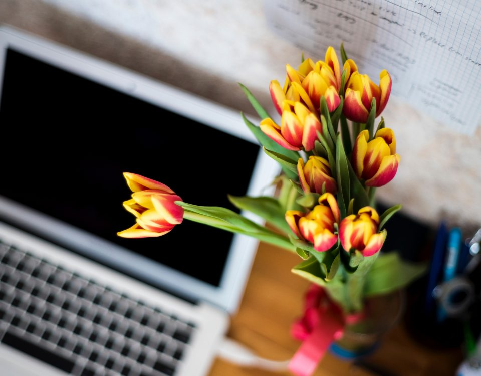 blog laptop open but off in the background on a desk with a bunch of yellow and red flowers in focus at front of picture. Photo shot from above