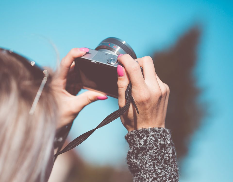 woman taking photos with a blue background
