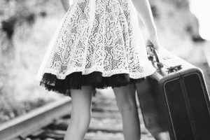 little girl in a lacy whitedress with underskirt can only be seen from waist down walking along a train track carrying a suit case. photo in black and white