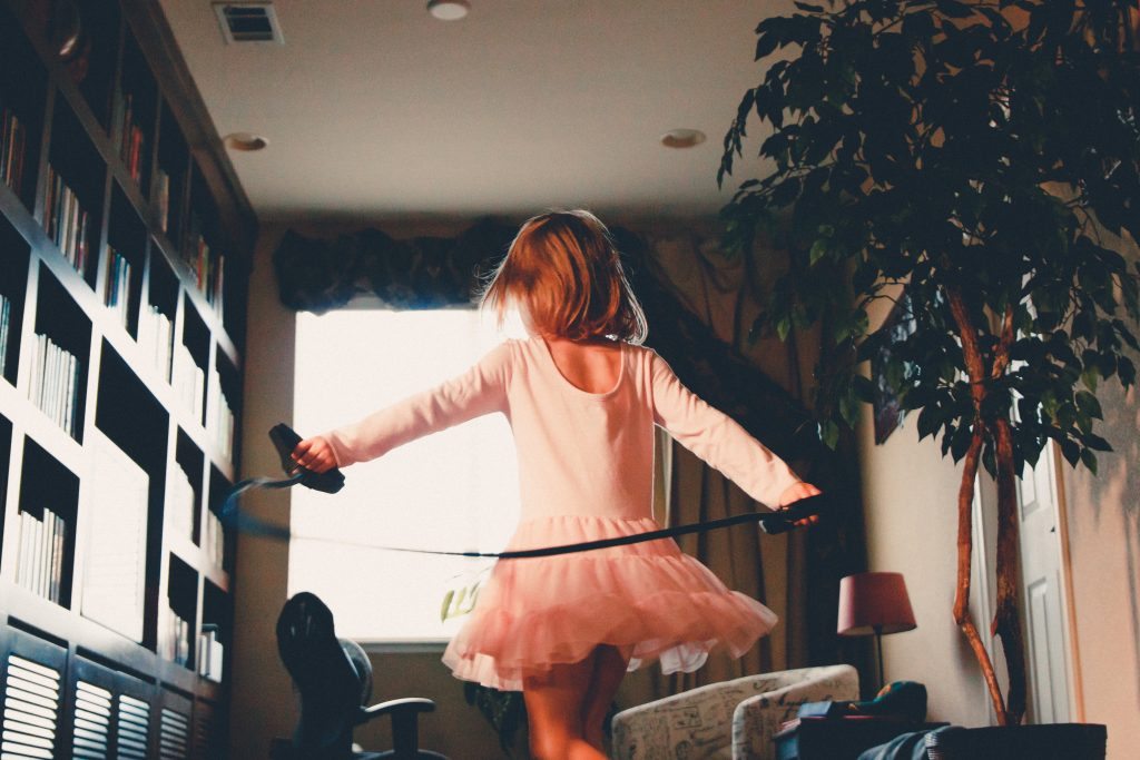 young girl with her back to the camera in a hall way with bookshelves one side a window behind her and a plant on the right in a pink tutu and holding her arms out behind her with a skipping rope in them