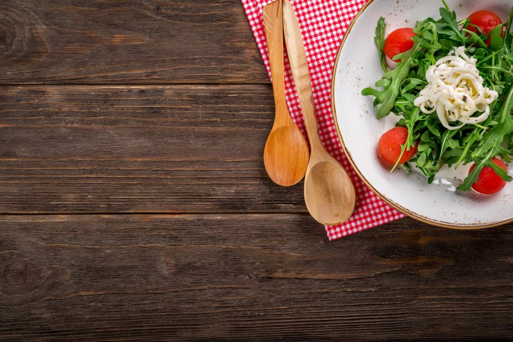 a wooden board with two lighterwooden sppons on a red gingham cloth and a white plate on top with salad on
