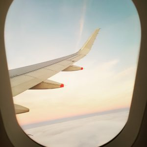 the wing of an airplane seen from the plane window at sunrise