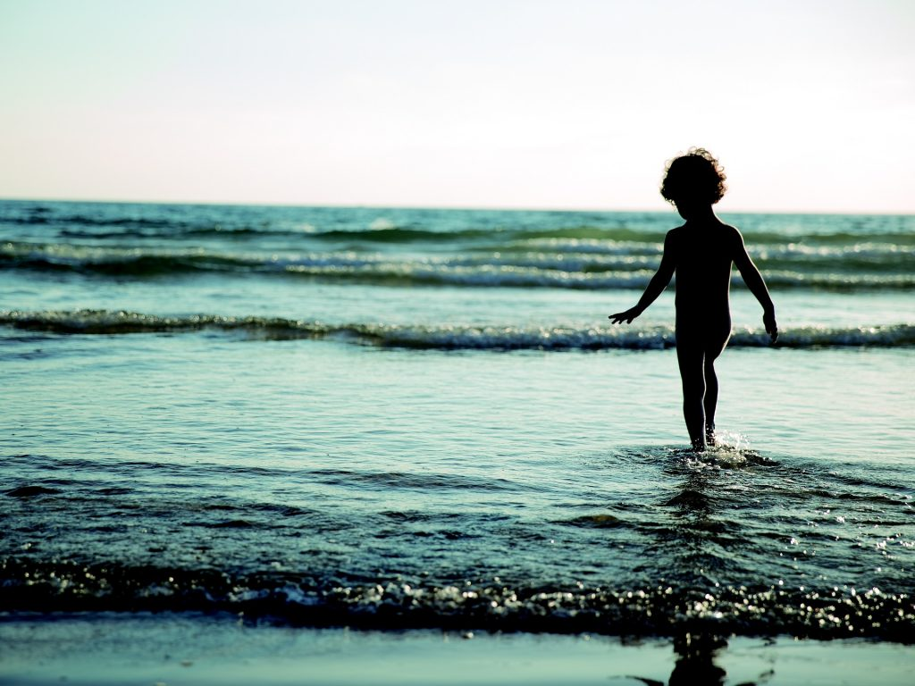 a silhouette picture of a child playing in the small waves of the sea