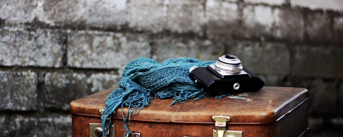 a grey brick wall and in front is a brown leather case with a blue scar and dslr camera on top