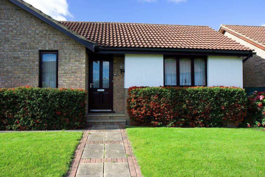 a picture of a bungalow with a grass front lawn