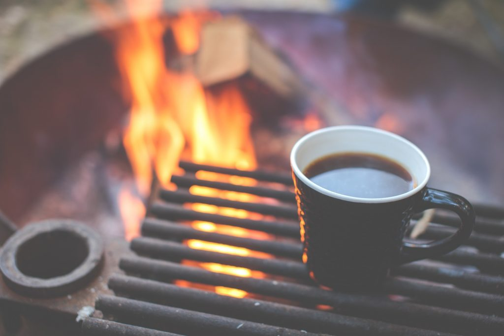 a bbq with a flame coming up with a coffee on the grill