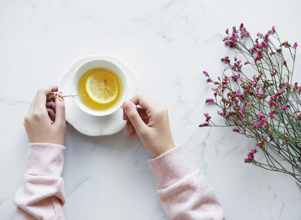 a woman's hands holding a cup of herbal tea with some dried pink flowers next to them on a marble back drop