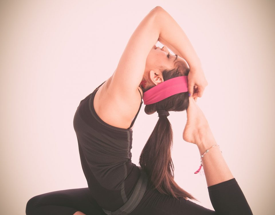 a woman in fitness gear reaching over behind her head to grab her foot