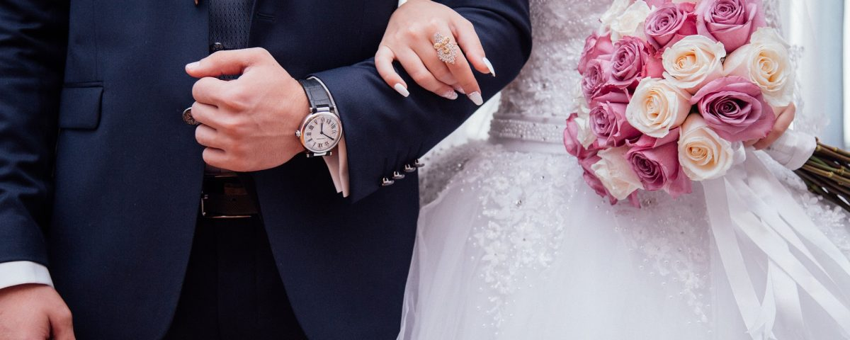 a bride and grooms bodies linked arms in their outfits. bridge is holding pink and white roses