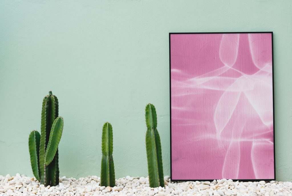 a side board with cacti and a pink picture in a frame with a mint wall behind