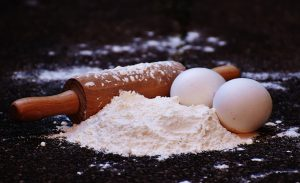 a black surface with a pile of flour, two eggs and a rolling pin