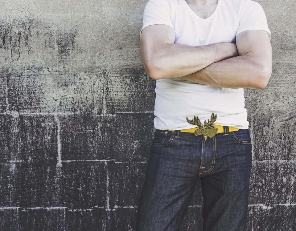 a man leaning against a wall with folded arms wearing jeans and a white tshirt