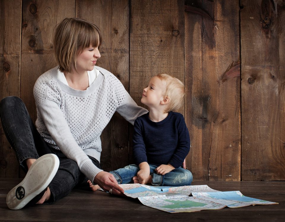 a woman sat on the floor with a child looking at a map