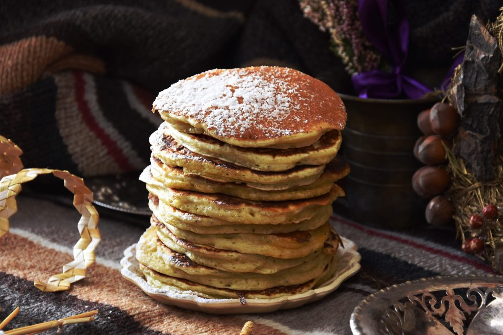 a stack of american style pancakes with icing sugar made from banana. vegan