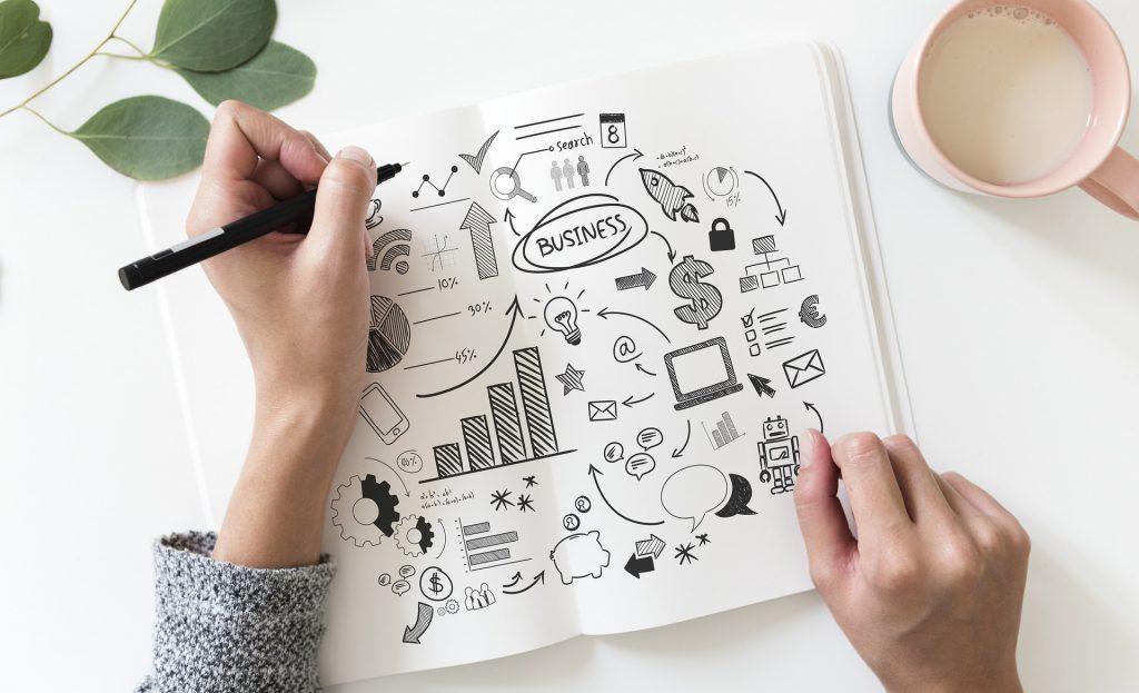 a woman doodling a plan in an open journal
