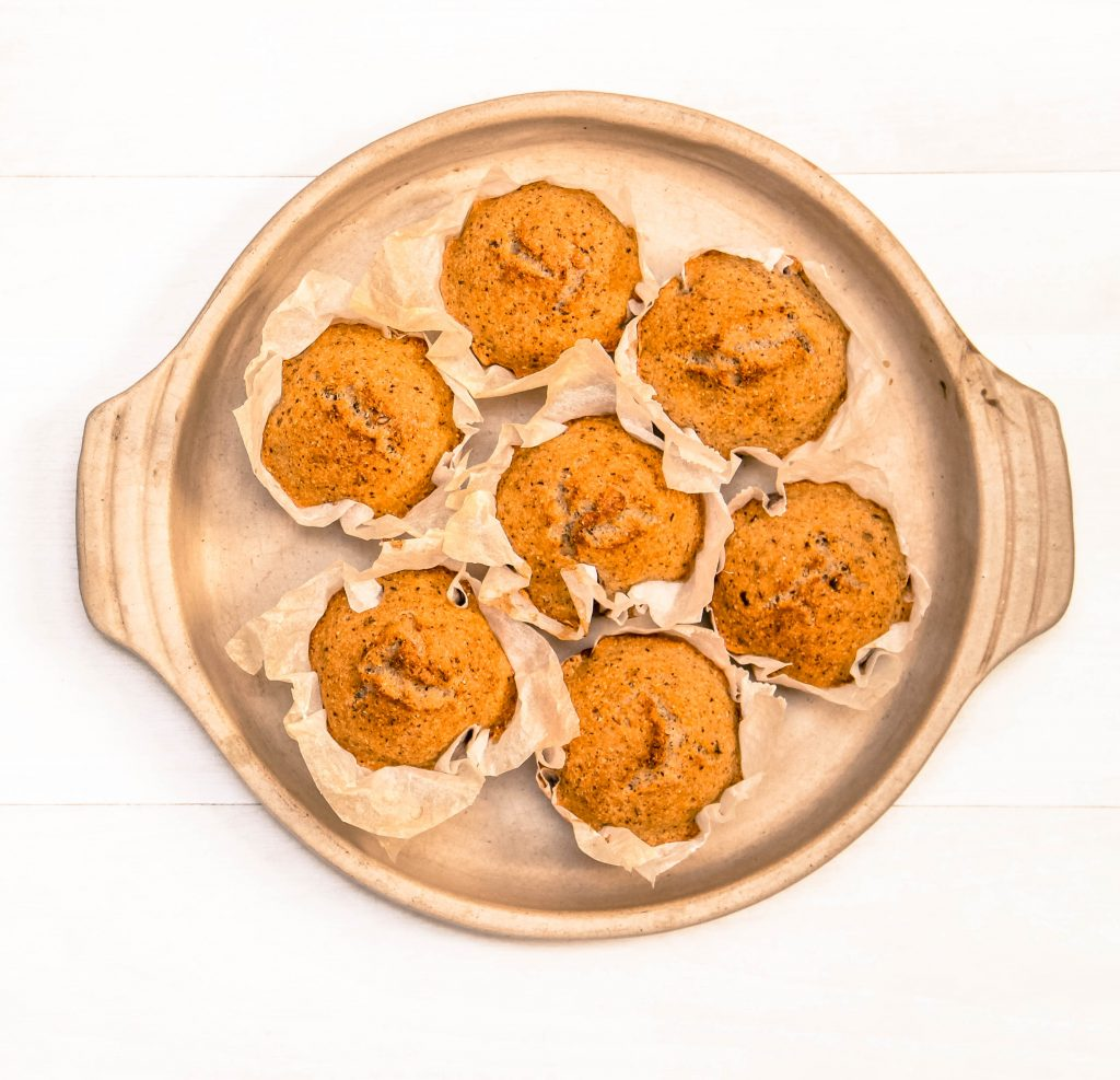 an oven dish full of savoury paper wrapped muffins. top view