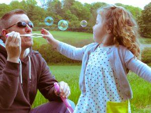 Alyssa popping bubbles blow by a friend