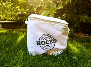 a white cool bag with rocks drinks written on it say on the grass in sunlight