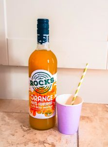 orange rocks drinks next to a cup and straw on marble floor