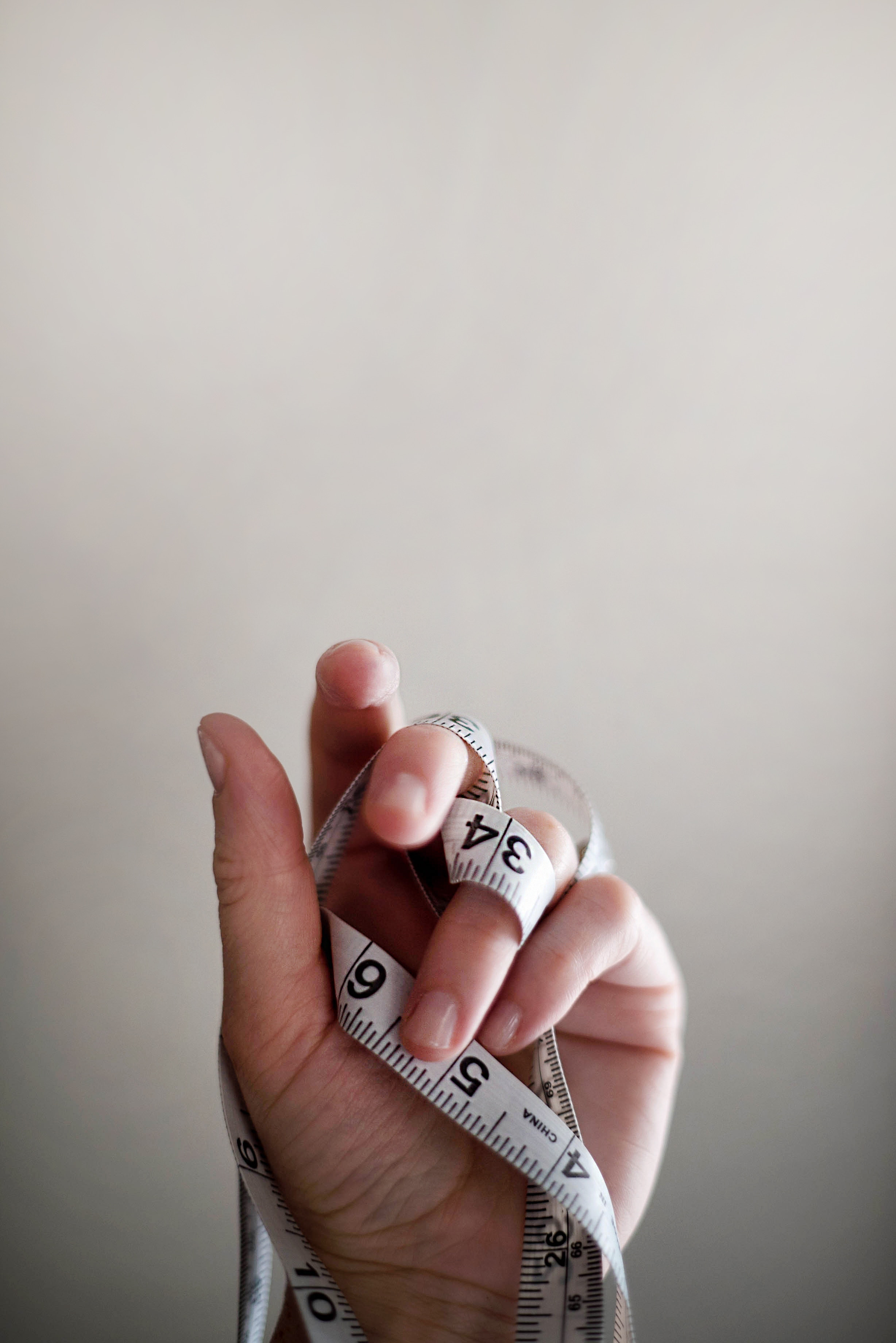 a hand holding a tape measure