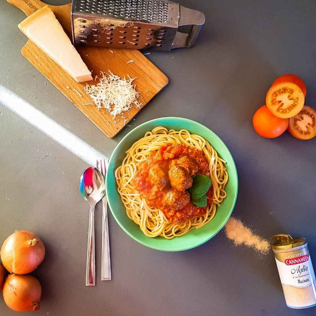 a flat lay of a bowl of vegetarian italian meatballs with spaghetti with parmesan raw ingredients and the garlic powder