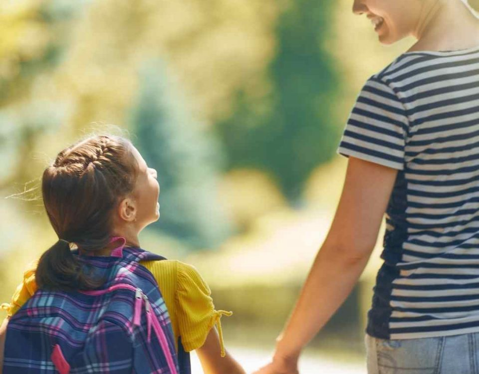mum holding childs hand walking