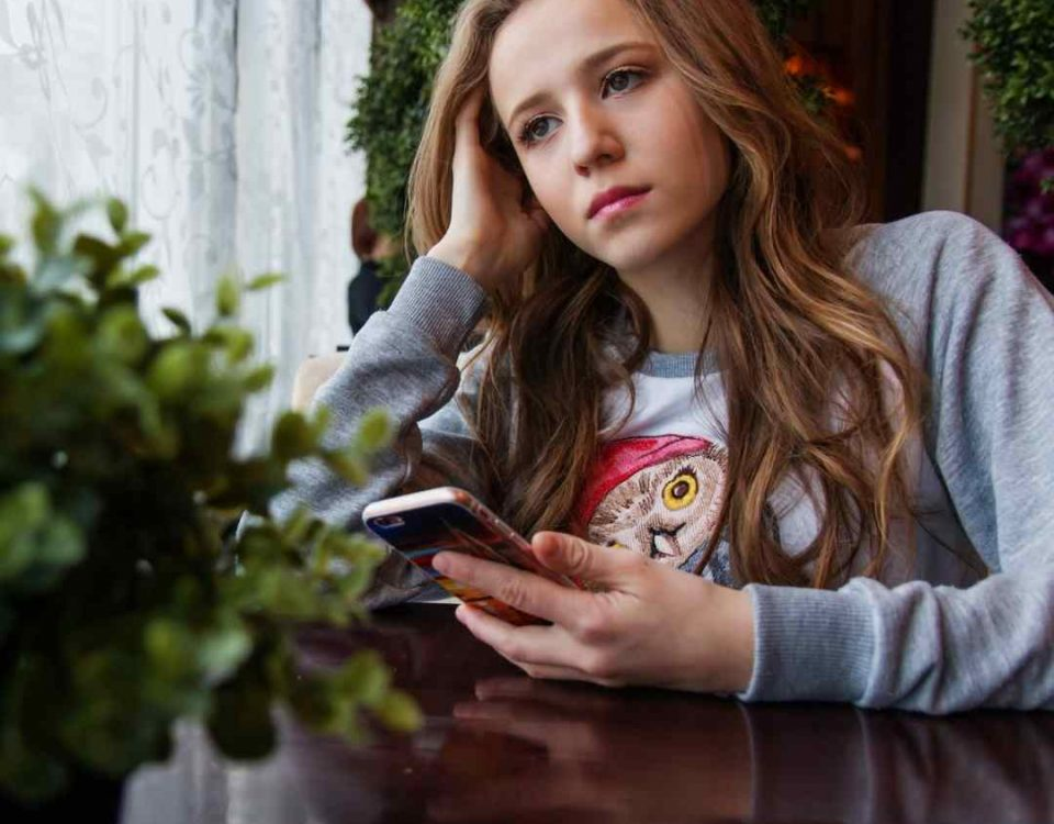 teenage girl with a phone looking out of a window