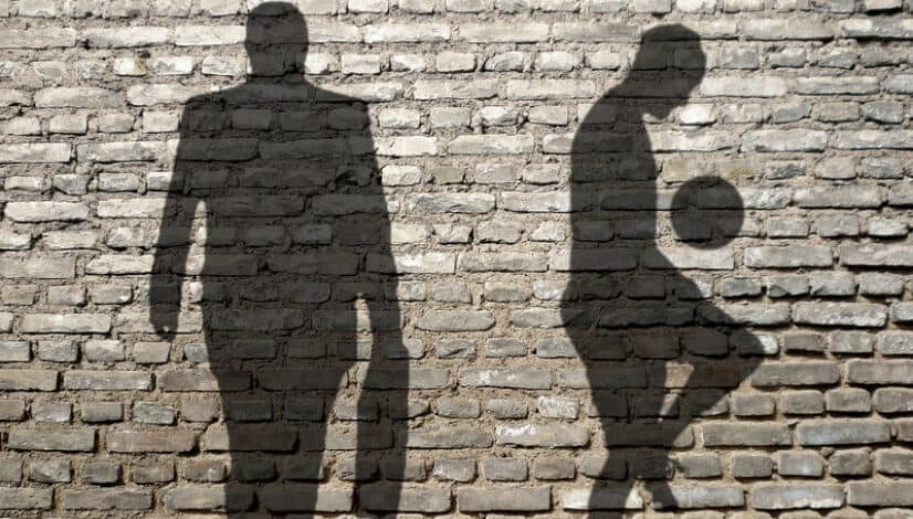 The shadow of a football player and an agent on a brick wall