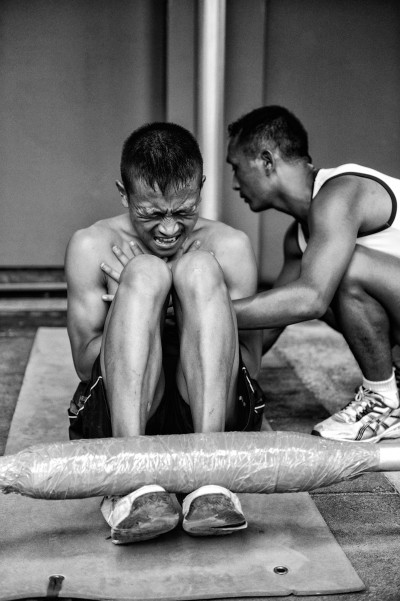A young Nepali boy fighting through the required minimum of 70 sit-ups in two minutes, closely observed by a physical training instructor (PTI) who makes sure elbows are kept close to the body and the entire range of motion from ground to knees is completed