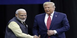 """Prime Minister Narendra Modi and President Donald Trump shake hands after introductions during the """"Howdi Modi"""""""