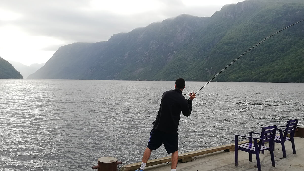 Guy fishing in lake with mountains