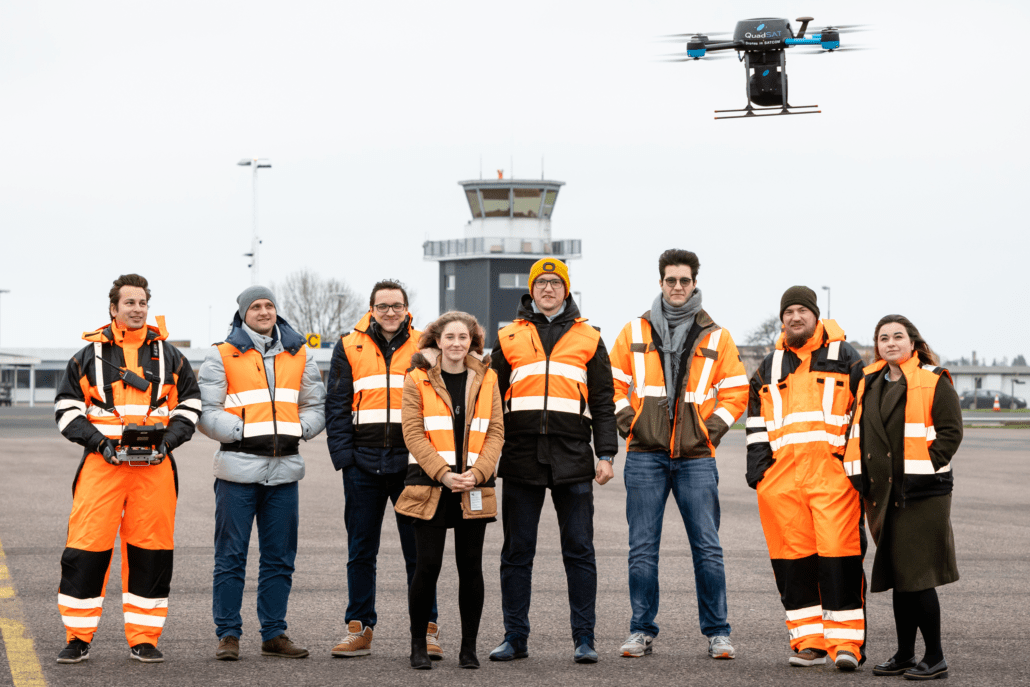 Team photo in front of airport with drone flying