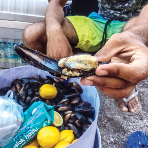 Man selling mussels and rice on the beach.