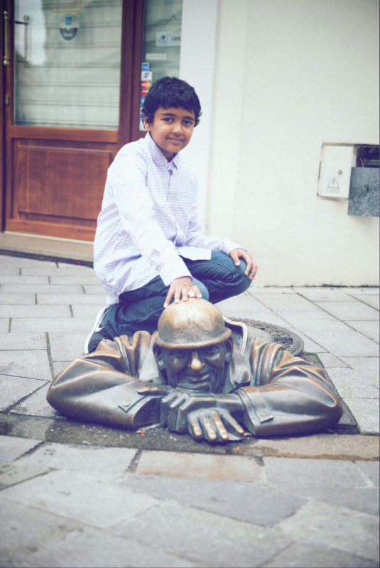 Asad, 9, poses with a popular statue of a man exiting a sewer in Bratislava