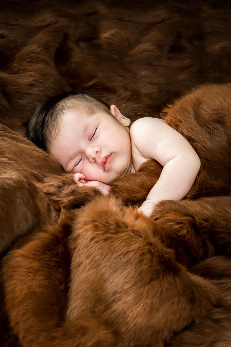 Sleeping newborn snuggled in heirloom coat