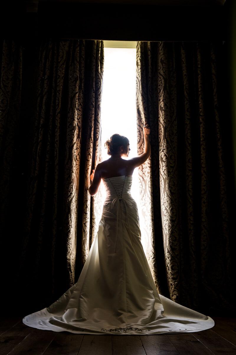 Bride window pose, bridal gown exposure