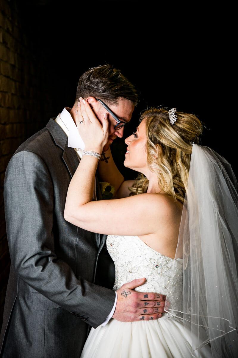 bride holds grooms head in her hands