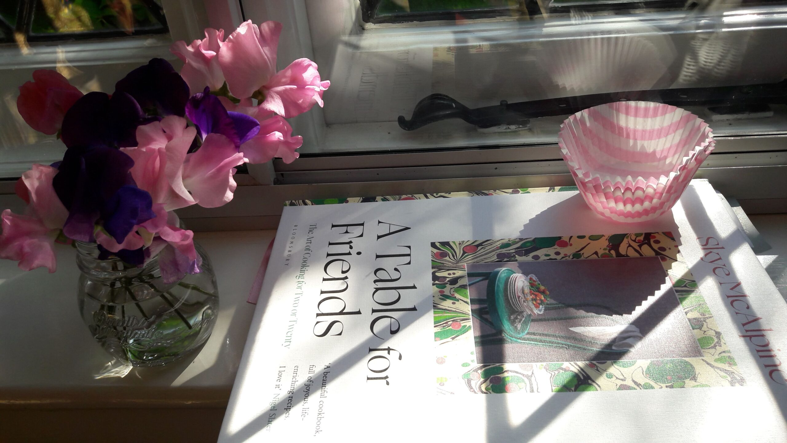 A table for friends cookbook on a window sill | Cookbook translation