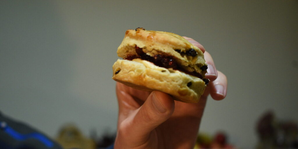 Eating a raspberry and clotted cream scone as a sandwich