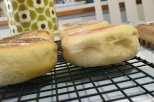 English muffins cooling on a rack on the dining table