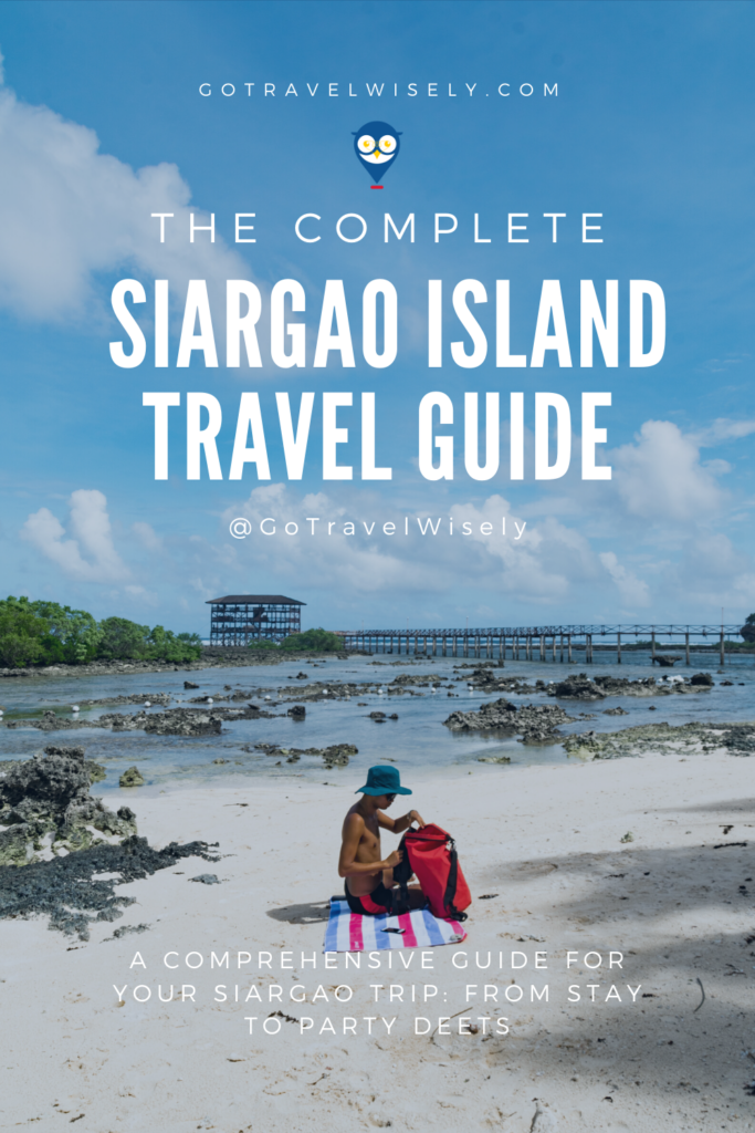 man checking his waterproof bag on beach while sitting on his travel towel (Siargao travel guide)