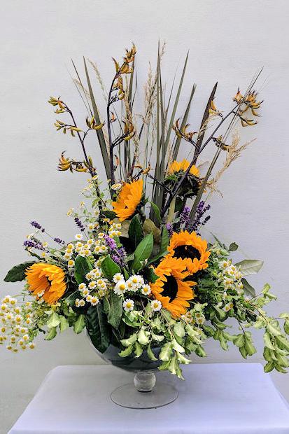 Pedestal arrangement with small sunflowers.