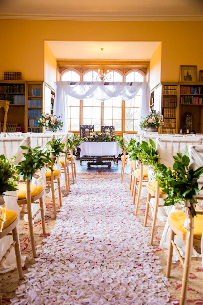 Rose petals covering wedding aisle in the Library, at Delapre Abbey.